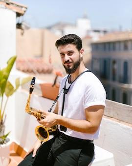 Mittlerer schussmann, der mit saxophon sitzt