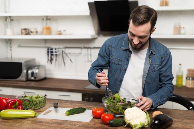 Mittlerer schussmann, der salat zubereitet