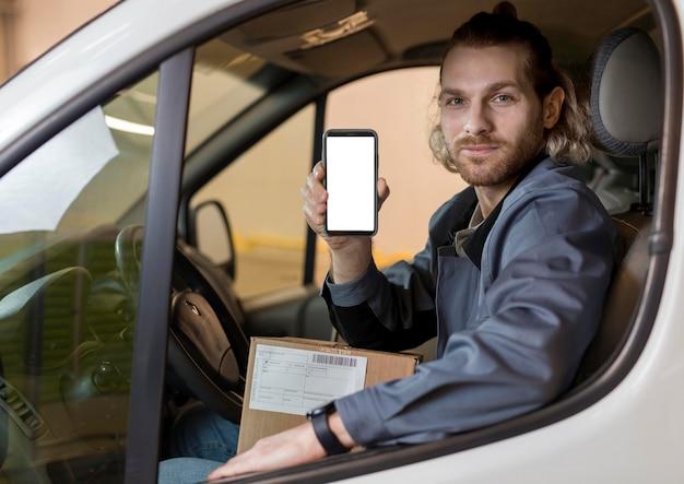 Mittlerer schussmann, der smartphone hält