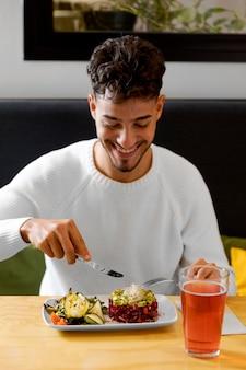 Mittlerer schussmann, der vegetarisches essen isst