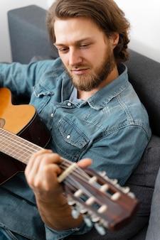 Mittlerer schussmann, der zu hause gitarre spielt