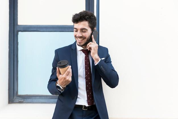 Mittlerer schussmann mit kaffee sprechend am telefon