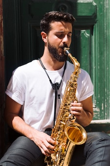 Mittlerer schussmusiker, der das saxophon sitzt und spielt