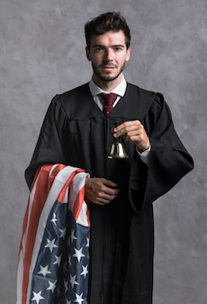 Mittlerer schussrichter in der robe mit flagge und glocke