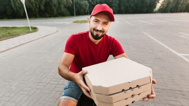 Mittlerer schusssmiley-lieferbote mit pizza
