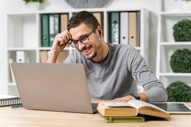 Mittlerer schusssmileykerl, der mit seinem laptop studiert