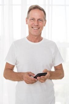 Mittlerer schusssmileymann, der einen smartphone hält