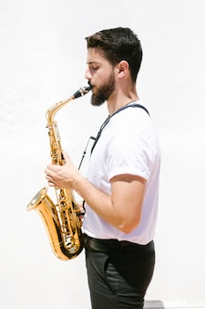 Mittlerer seitlicher musiker des schusses, der das saxophon spielt
