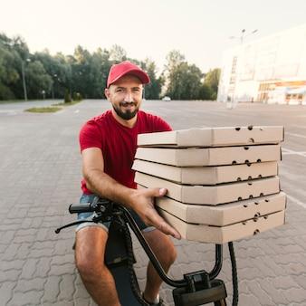 Mittlerer shotdelivery kerl, der pizzakästen hält