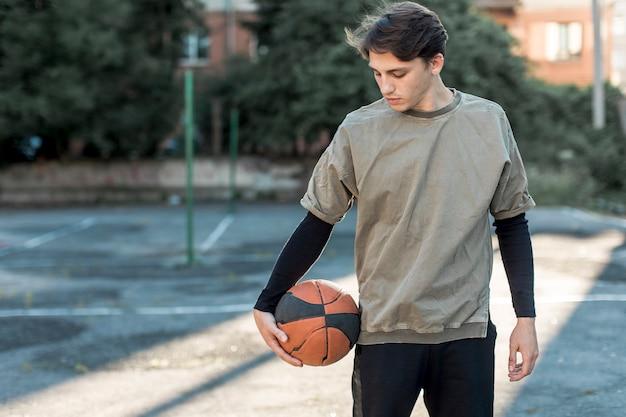 Mittlerer städtischer basketballspieler des schusses