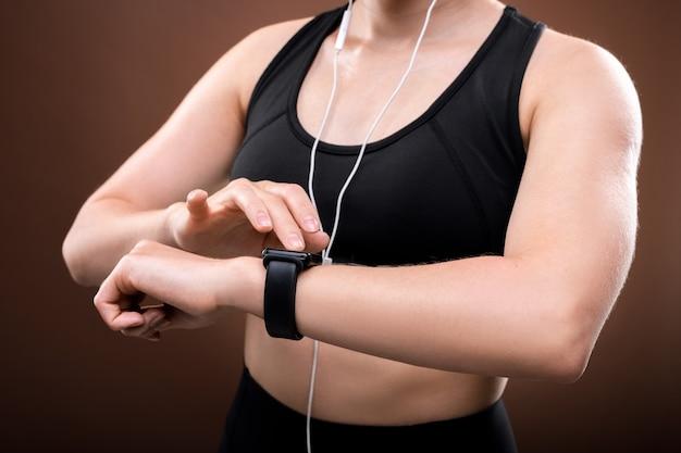 Mittlerer teil der jungen sportlerin in activewear und kopfhörern, die ihr fitbit am handgelenk vor dem joggen im freien einschaltet