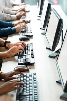 Mittlerer teil der kollegen, die am computer arbeiten