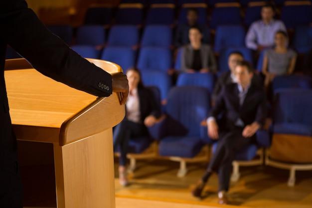 Mittlerer teil des männlichen geschäftsführers, der eine rede im konferenzzentrum hält