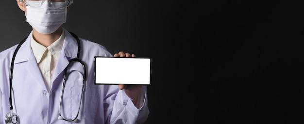Mittleres alter der asiatischen ärztin, die handy-bildschirm zeigt, um etwas zu kommunizieren