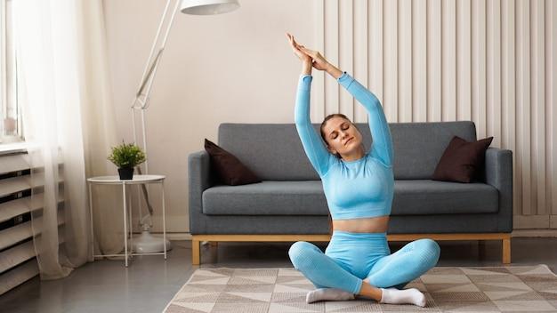 Mittleres erwachsenes frauentraining zu hause. horizontale form, volle länge, seitenansicht. glückliche frau, die fitness und yoga zu hause tut.