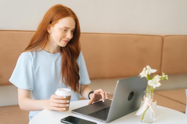Mittleres porträt einer glücklichen jungen schönen frau, die auf dem laptop tippt und kaffee aus der tasse trinkt, während sie in einem gemütlichen café aus der ferne arbeitet. hübsche kaukasische dame der rothaarigen entfernt, die arbeitet oder studiert.