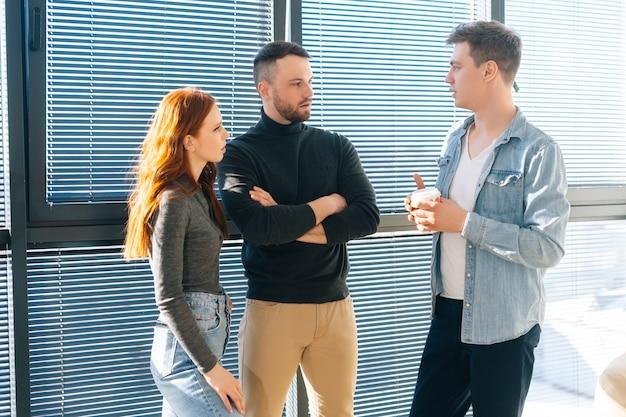 Mittleres porträt von drei positiven jungen geschäftsleuten, die sich während der kaffeepause im modernen büro unterhalten. fröhliche mitarbeiter genießen angenehme kommunikation, diskutieren projekt in fensternähe.
