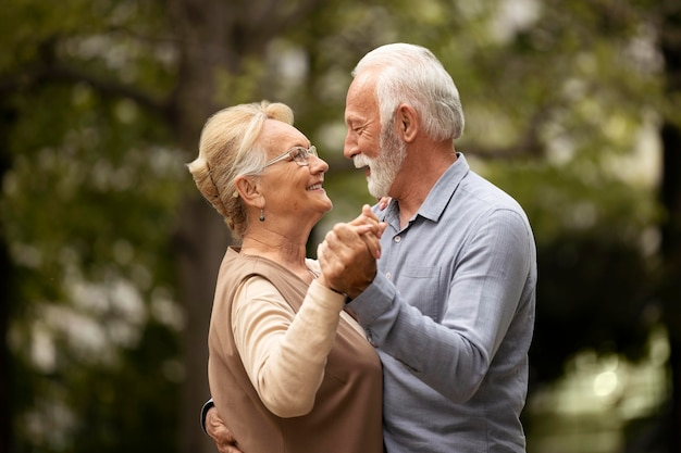 Mittleres schuss älteres paar, das draußen tanzt