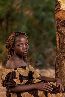 Mittleres schuss afrikanisches mädchen, das nahe baum aufwirft