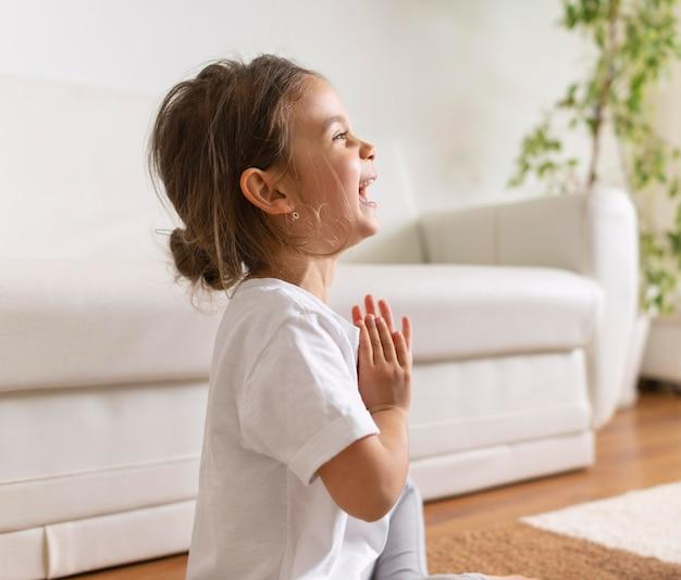 Mittleres schuss glückliches mädchen, das meditiert