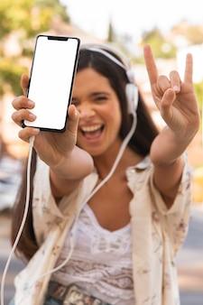 Mittleres schuss glückliches mädchen mit smartphone