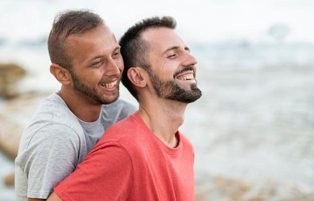 Mittleres schuss glückliches paar am meer