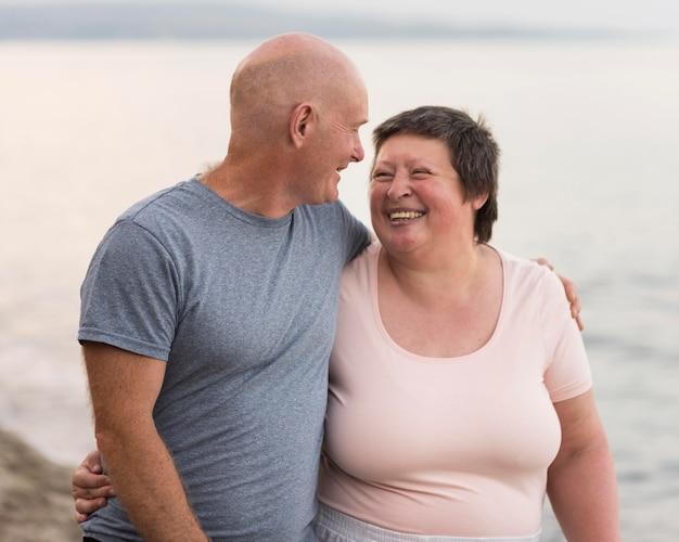 Mittleres schuss glückliches paar am strand