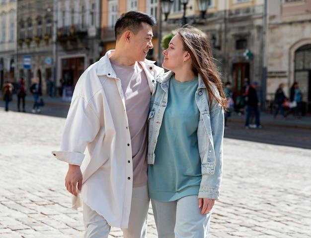 Mittleres schuss glückliches paar in der stadt