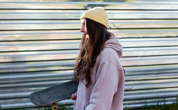 Mittleres schuss jugendlich mädchen, das skateboard hält