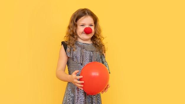 Mittleres schuss kleines mädchen, das clownnase trägt