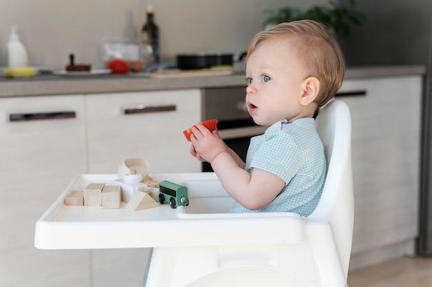 Mittleres schuss kleinkind, das tomate isst