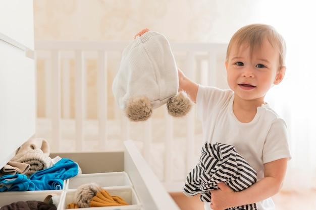Mittleres schuss niedliches baby, das kleidung von schublade nimmt