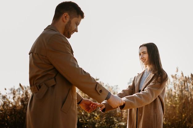 Mittleres schuss romantisches paar, das hände hält