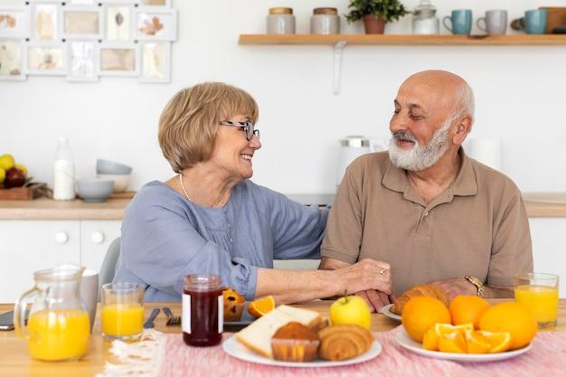 Mittleres schuss smiley älteres paar am tisch