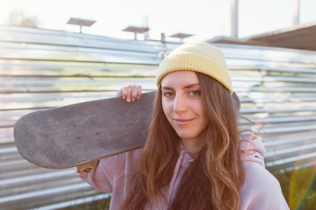 Mittleres schuss-smiley-mädchen, das skateboard hält