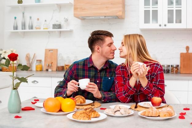 Mittleres schussglückliches paar, das frühstückt