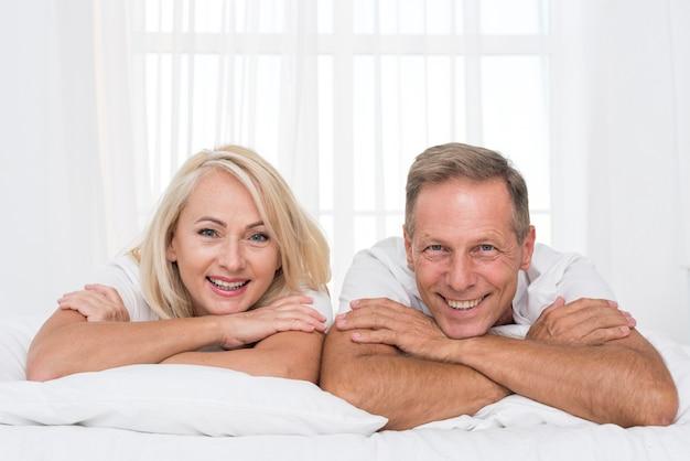 Mittleres schussglückliches paar, das im schlafzimmer aufwirft