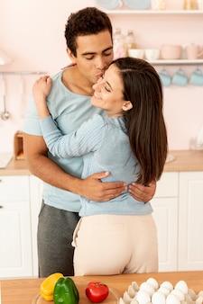 Mittleres schussglückliches paar, das in der küche umarmt