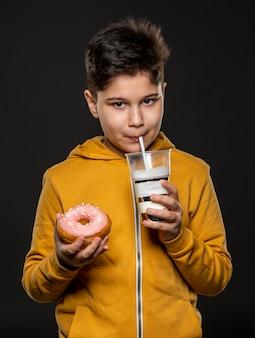 Mittleres schusskind, das getränk und donut hält