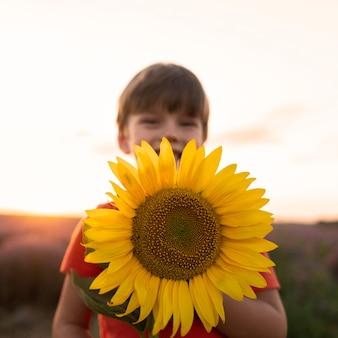 Mittleres schusskind, das sonnenblume hält