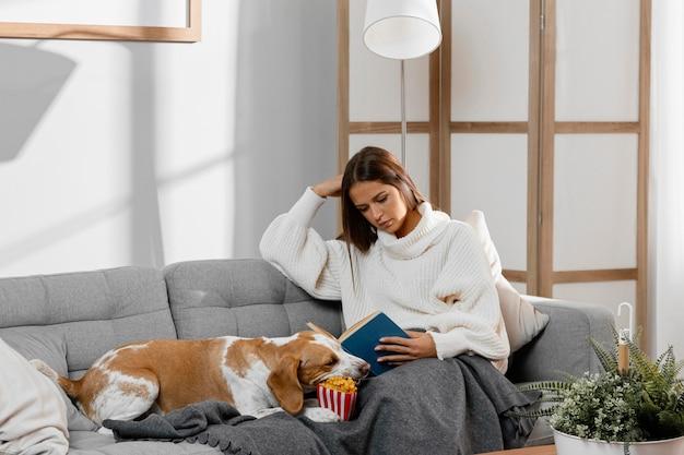 Mittleres schussmädchen auf der couch mit hund