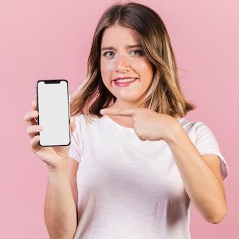 Mittleres schussmädchen, das auf das telefon zeigt