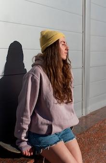 Mittleres schussmädchen, das auf skateboard sitzt