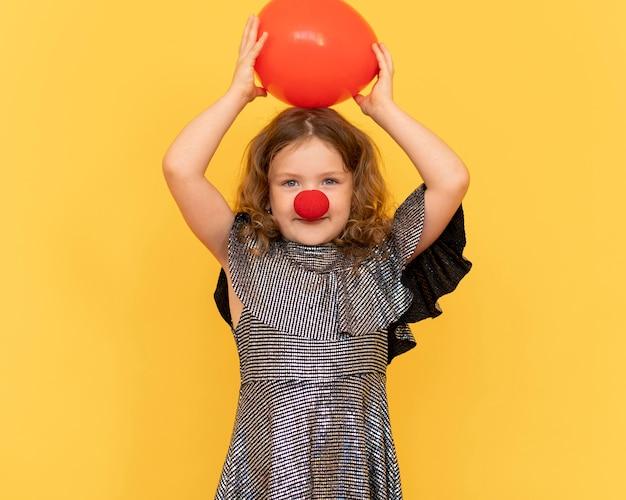 Mittleres schussmädchen, das clownnase trägt