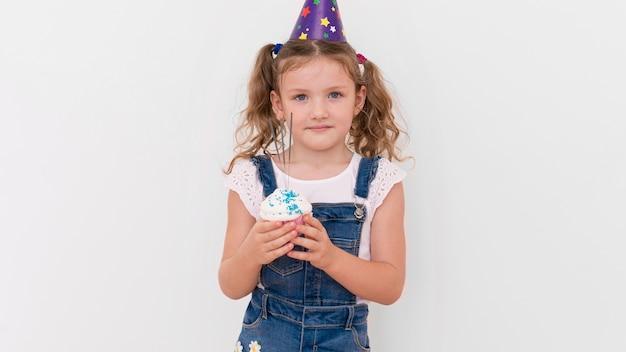 Mittleres schussmädchen, das cupcake hält