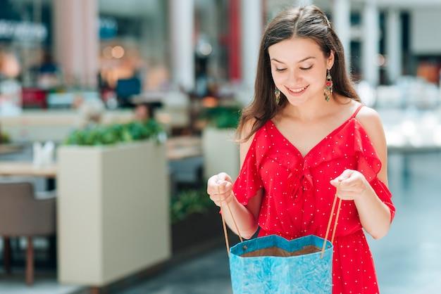 Mittleres schussmädchen, das einkaufstasche lächelt und hält