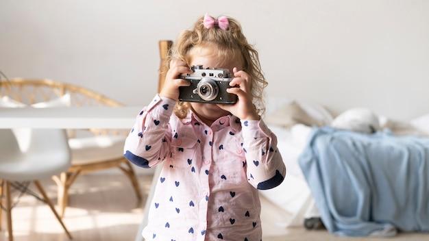 Mittleres schussmädchen, das fotos mit ihrer kamera macht