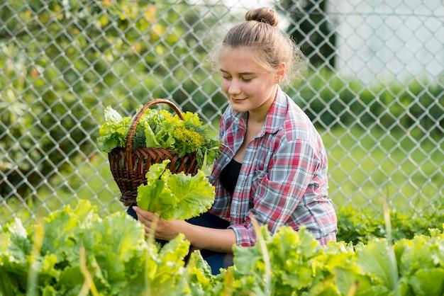 Mittleres schussmädchen, das frischen salat aufnimmt