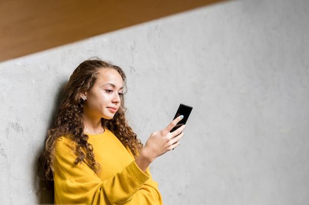 Mittleres schussmädchen, das ihren smartphone betrachtet