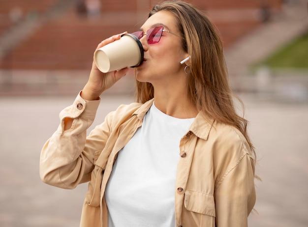 Mittleres schussmädchen, das kaffee trinkt